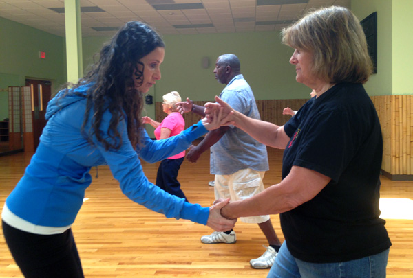 Tai Chi instructor Barrie Austin is correcting a form of the class student